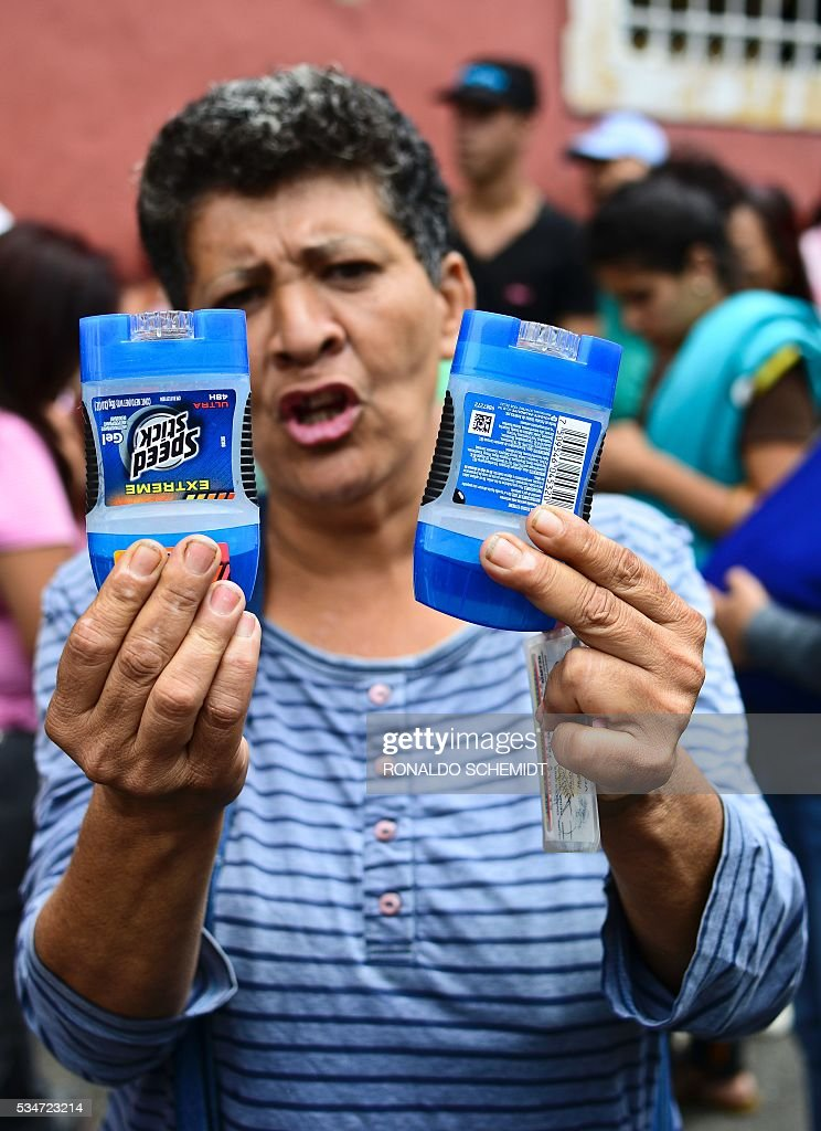 A woman protests as she holds up two deodorants purchased after five hours standing in line to buy basic food and household items outside a supermarket in the poor neighborhood of Lidice, in Caracas, Venezuela on May 27, 2016. / AFP / RONALDO
