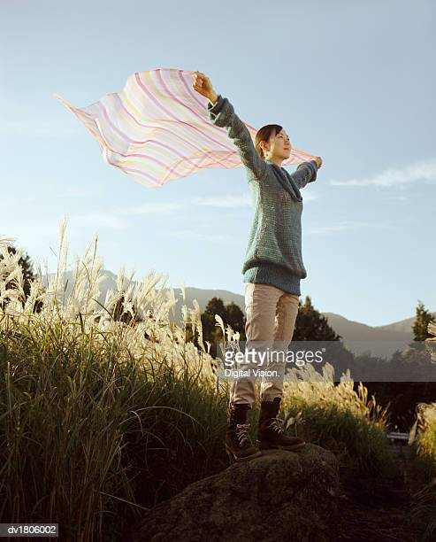 Woman Proudly Standing on a Boulder Holding Out a Striped Piece of Fabric Behind Her