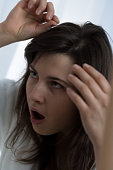 Shocked young woman pulling a gray hair