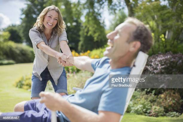 Woman pulling novio de silla de jardín