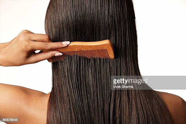 woman pulling comb through her hair