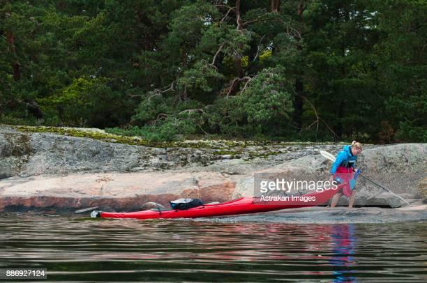 Woman pulling kayak on lakeshore