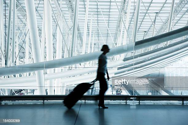 Woman Pulling Luggage at Airport, Blurred Motion, Blue Toned Image