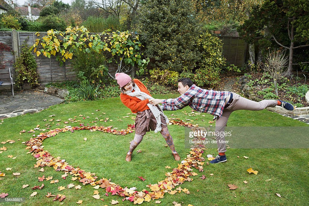 Woman pulling man into heart of autumn leaves. : Stock Photo
