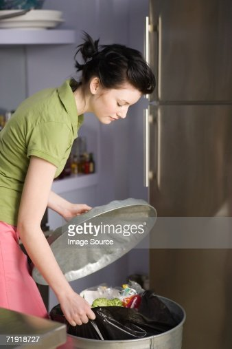 Woman pulling out rubbish bag from bin : Stock Photo