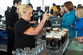 Woman pulling pints of Guinness at Gravity Bar at Guinness Storehouse.
