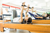 Young woman pulling resistance bands while lying on reformer machine at gym