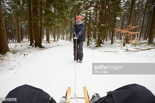 Woman pulling someone on sled
