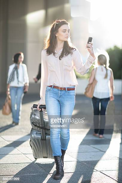 Woman pulling suitcase and looking at cell phone in the city