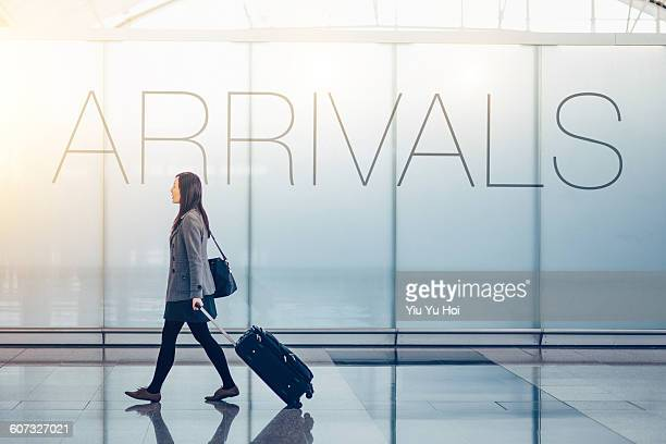 Woman pulling suitcase in the airport arrival hall