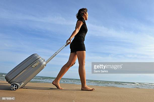 Woman pulling suitcase on beach