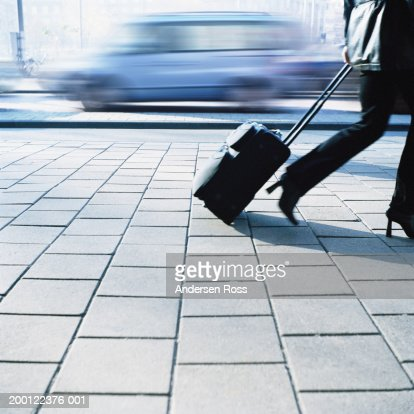 Woman pulling suitcase past traffic, low section (blurred motion)