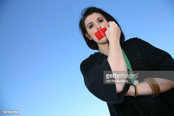 Woman pulling tape off her mouth