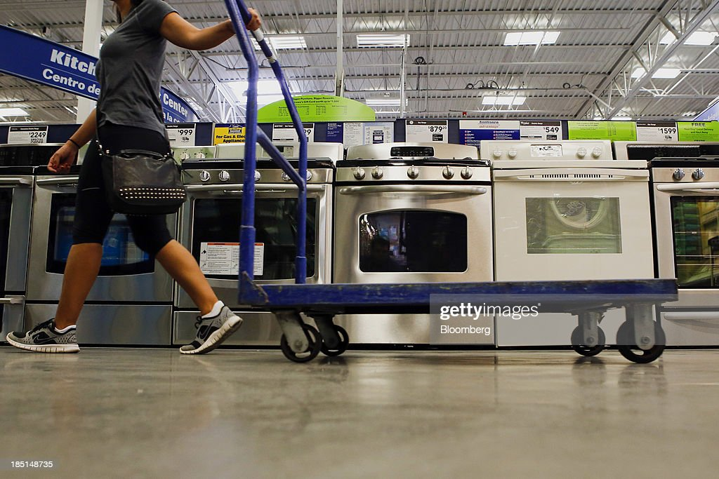 A woman pulls a cart past a General Electric Co. gas range and oven, center, displayed for sale at a Lowe's Cos. store in Torrance, California, U.S, on Thursday, Oct. 17, 2013. General Electric Co. is scheduled to release earnings figures on Oct. 18. Photographer: Patrick T. Fallon/Bloomberg via Getty Images