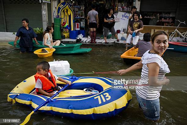 A woman pulls an inflatable raft carrying a child through floodwaters in Bangkok on November 8 2011 Thailand's prime minister said she would miss an...