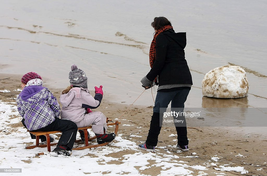 A woman pulls children on a sled on the snow-covered Strandbad Wannsee beach during its opening day for the year on March 29, 2013 in Berlin, Germany. Despite continued unseasonably cold temperatures in the country, organizers opened the beach for bathers in time for the last weekend of March, when Easter Sunday is expected to be colder than the previous Christmas Day had been.