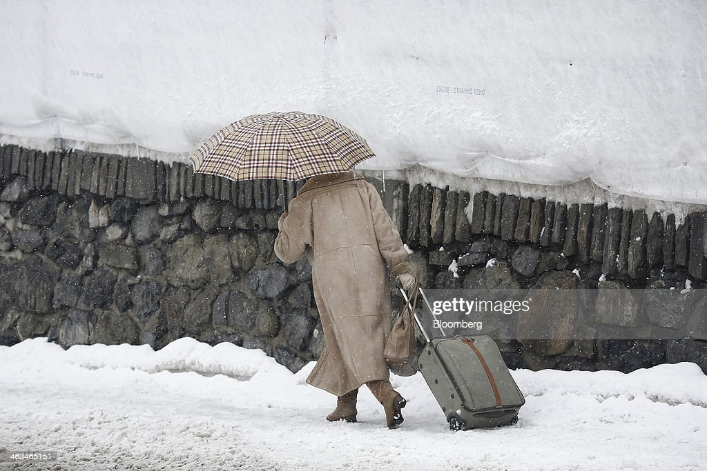A woman pulls her suitcase along a snow covered path as she shelters under an umbrella in Davos, Switzerland, on Friday, Jan. 17, 2014. Next week the business elite will gather in the Swiss Alps for the 44th annual meeting of the World Economic Forum (WEF) in Davos for the five day event which runs from Jan. 22-25. Photographer: Simon Dawson/Bloomberg via Getty Images
