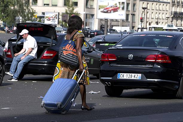 A Woman Pulls Her Suitcase As She Walks Past Taxi Vehicles Blocking - Taxi porte maillot
