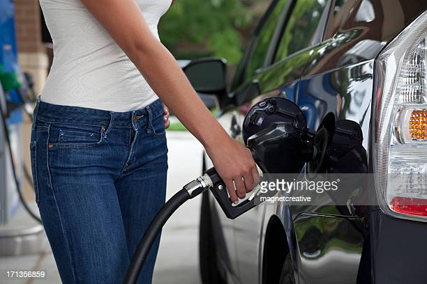 A woman pumping gas to her car
