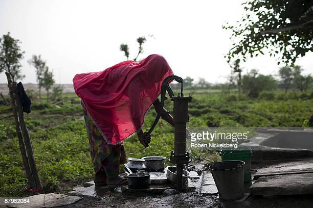 A woman pumps water from a tube well to clean dishes in a slum area near a newly dug roadway April 21 2009 where agricultural areas she and members...