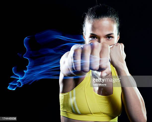 woman punching air with fist on fire