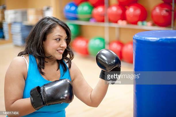 Woman punching bag in gym