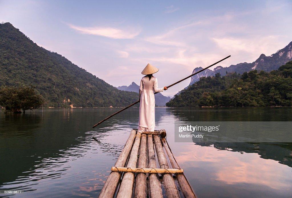 woman punting bamboo raft across lake