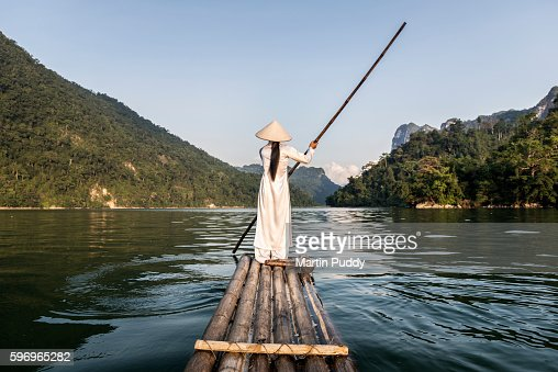 woman punting bamboo raft across lake