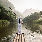 woman punting bamboo raft along river