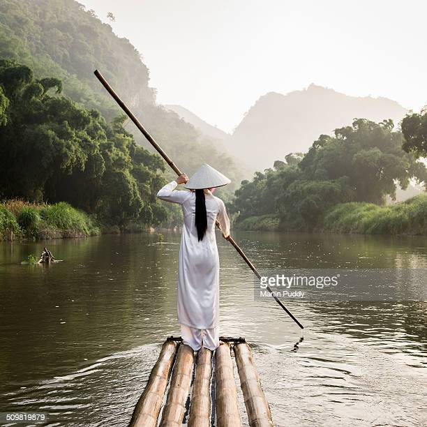 woman punting bamboo raft along river