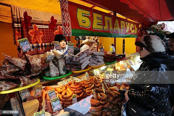 A woman purchases food products from Belarus at a street market in Saint Petersburg on December 11 2014 AFP PHOTO / OLGA MALTSEVA