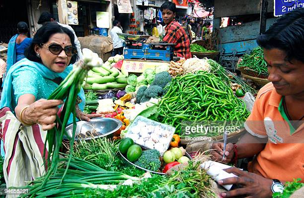 A woman purchases vegetables at a traditional vegetable market in Mumbai India on Thursday Nov 29 2007 India's economy grew last quarter at the...