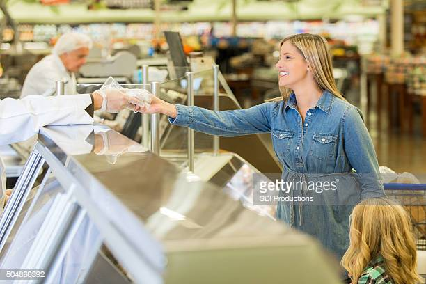 Woman purchasing meat from deli counter in supermarket