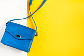 Woman purse on colorful background. Blue and yellow pastel colors, top view, copy space