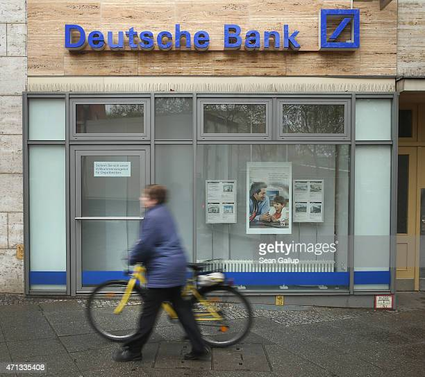A woman pushes a bicycle past a branch of German bank Deutsche Bank on April 27 2015 in Berlin Germany Deutsche Bank announced earlier in the day...