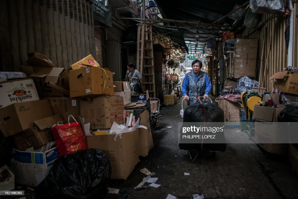 A woman pushes a cart loaded with items to be recycled in Hong Kong on February 20, 2013. Activists have claimed for years that Hong Kong lags behind the rest of the world on environmental issues ranging from recycling to lanes for cyclists. AFP PHOTO / Philippe Lopez