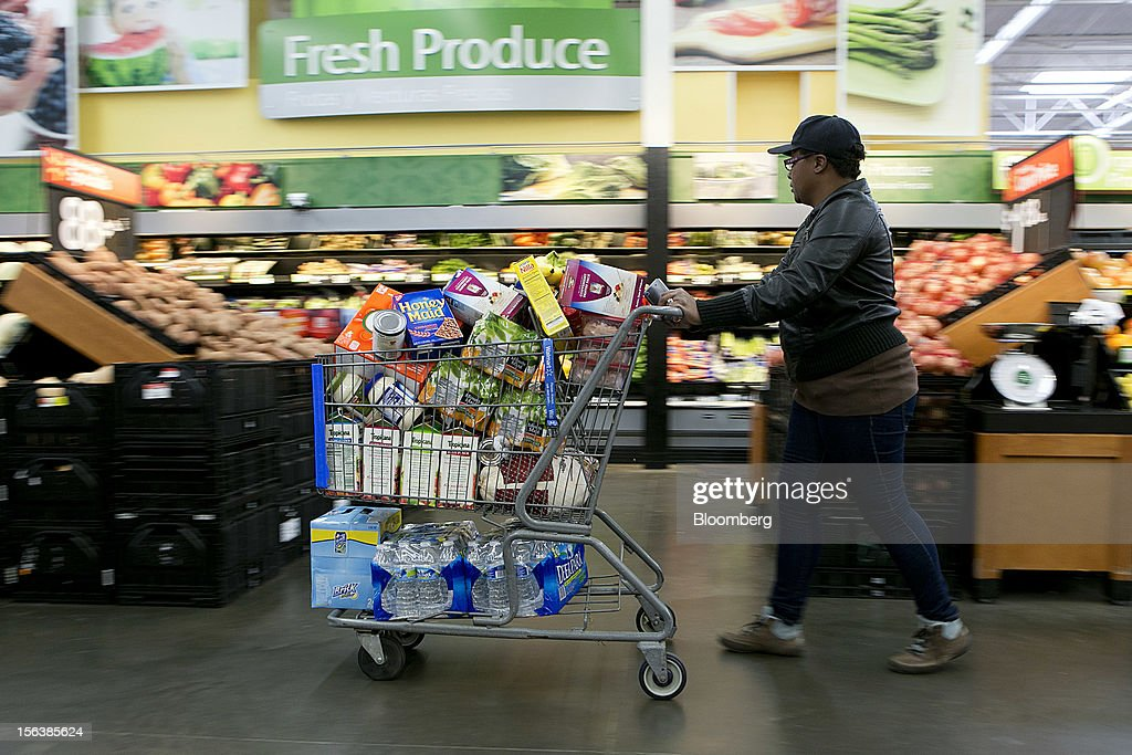 A woman pushes a cart though the produce section of a Wal-Mart store in Alexandria, Virginia, U.S., on Wednesday, Nov. 14, 2012. Wal-Mart Stores Inc. is scheduled to release earnings data on Nov. 15. Photographer: Andrew Harrer/Bloomberg via Getty Images