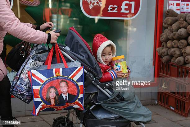 A woman pushes a child in a pram laden with shopping bags along Lewisham high street on December 5 2012 in London England The Chancellor of the...
