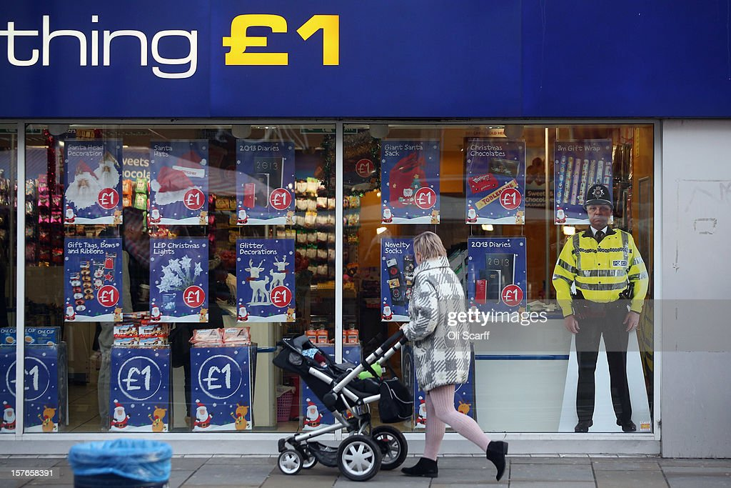 A woman pushes a pram past a discount retailer with a cardboard cut-out of a police officer in the window on Lewisham high street on December 5, 2012 in London, England. The Chancellor of the Exchequer George Osborne has stated that the United Kingdom's economy is still struggling during his autumn budget statement to Parliament.
