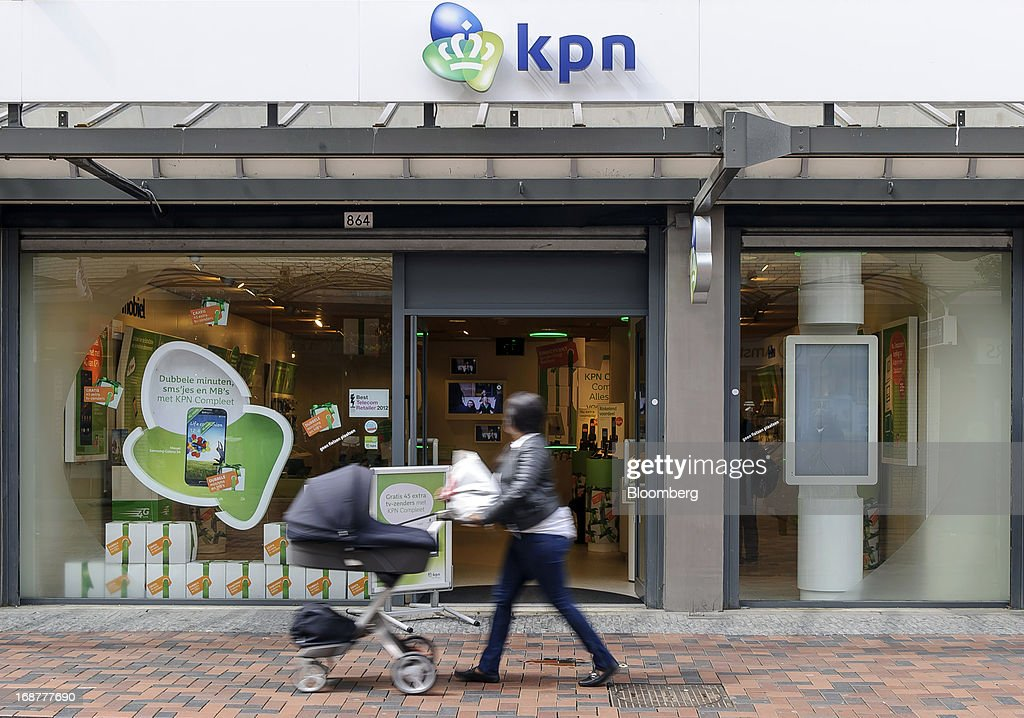 A woman pushes a pram past a KPN store, operated by the Dutch phone company Royal KPN NV in Amsterdam, Netherlands, on Tuesday, May 14, 2013. Euro-area data this week will probably reveal economic scars of the sovereign debt crisis confirming that the region is now suffering the longest recession since the single currency's creation. Photographer: Jock Fistick/Bloomberg via Getty Images