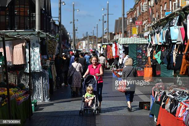 A woman pushes a pram through Walthamstow market on August 9 2016 in London England Walthamstow Market in north east London is believed to be the...