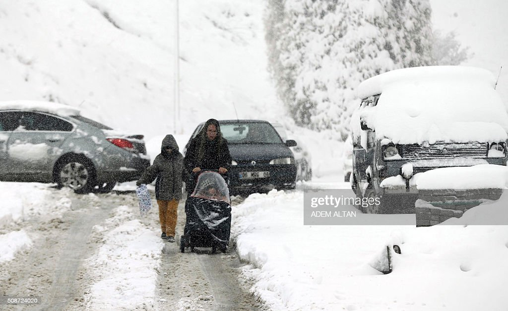 A woman pushes a pushchair with a baby as she walks beside a child under the snow in Ankara on February 6, 2016. / AFP / ADEM ALTAN