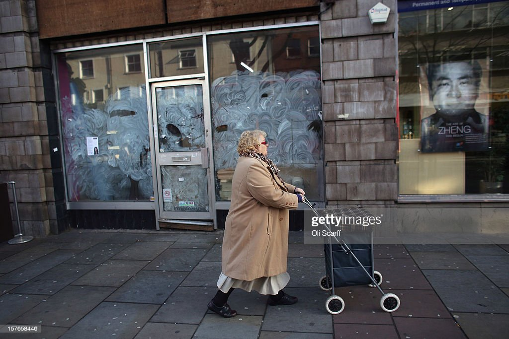 A woman pushes a shopping basket past a closed-down shop on Lewisham high street on December 5, 2012 in London, England. The Chancellor of the Exchequer George Osborne has stated that the United Kingdom's economy is still struggling during his autumn budget statement to Parliament.