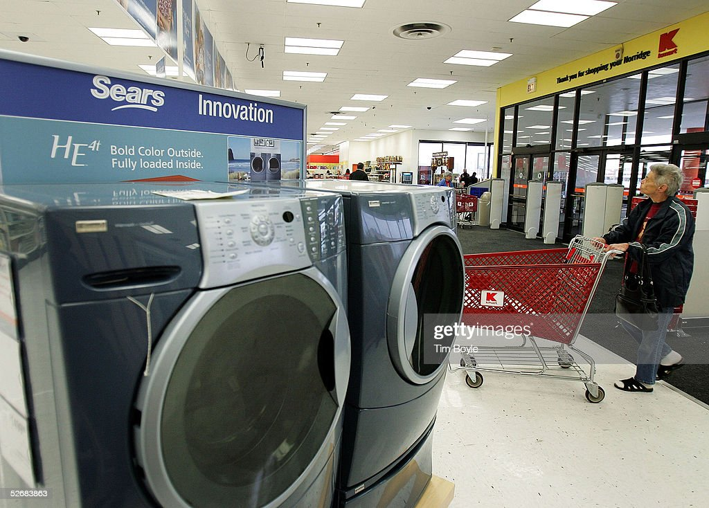 a woman pushes a shopping cart past a sears set in a newly revamped kmart with sears washer and dryer sale sets
