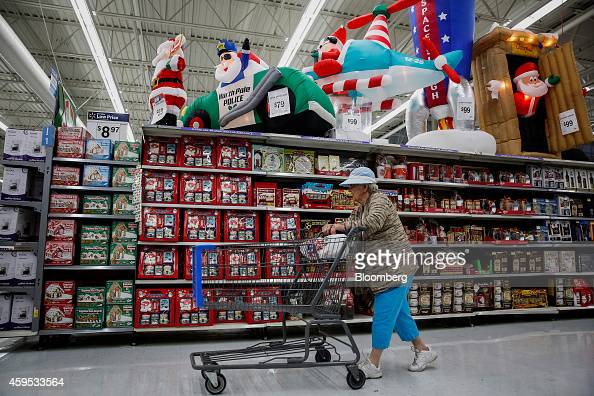 A woman pushes a shopping cart past Christmas decorations displayed for sale at a WalMart Stores Inc location ahead of Black Friday in Los Angeles...