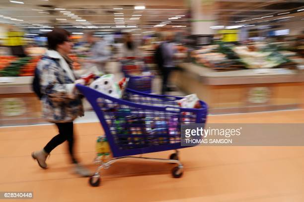 A woman pushes a shopping trolley as she walks in the aisles of an hypermarket store of French retail giant Carrefour in VilleneuvelaGarenne near...