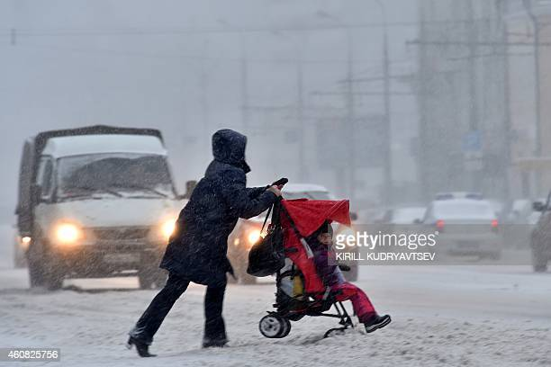 A woman pushes a stroller across a road during a heavy snowfall in Moscow on December 25 2014 The temperatures in Moscow reached today 8 C AFP...