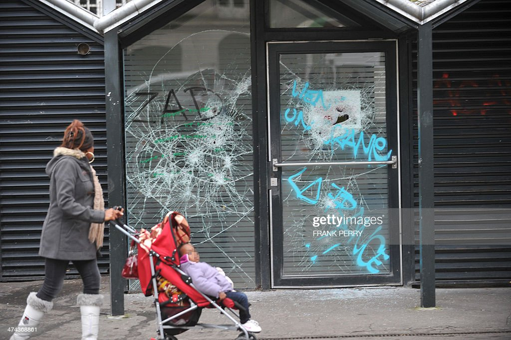 A woman pushes a stroller past a tramway station in Nantes, western France, on February 23, 2014 which was burnt down by protesters opposed to plans to build the new Notre-Dames-des-Landes airport for the French city of Nantes. Protesters smashed shop windows on February 22 and hurled paving stones at police, who answered with tear gas and rubber bullets. Tens of thousands of protesters against building the airport on protected swampland swarmed the western city's Petite Hollande square, the latest in a string of demonstrations against the pet project of Prime Minister Jean-Marc Ayrault. AFP PHOTO/FRANK PERRY