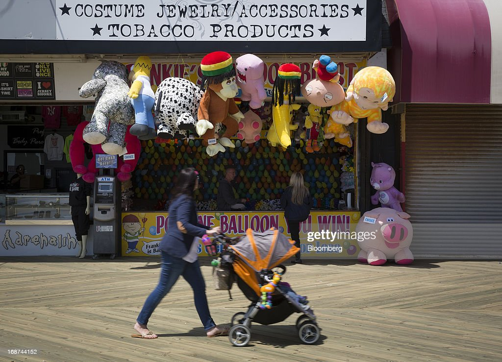 A woman pushes a stroller past games along the boardwalk in Seaside Heights, New Jersey, U.S., on Tuesday, May 14, 2013. Seaside Heights Mayor William Akers is looking forward to showing off the improvement as the prince visits, part of a week-long U.S. tour that also includes stops in Washington, Colorado and New York. Photographer: Scott Eells/Bloomberg via Getty Images