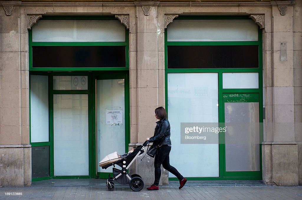 A woman pushes a stroller past the closed premises of a former Caixa Penedes bank branch in Barcelona, Spain, on Tuesday, Jan. 8, 2013. Banco Santander SA, Spain's biggest lender, will offer 263 million euros ($345 million) in stock to buy out minority investors in its Banco Espanol de Credito SA retail unit and close 700 local branches to cut costs. Photographer: David Ramos/Bloomberg via Getty Images